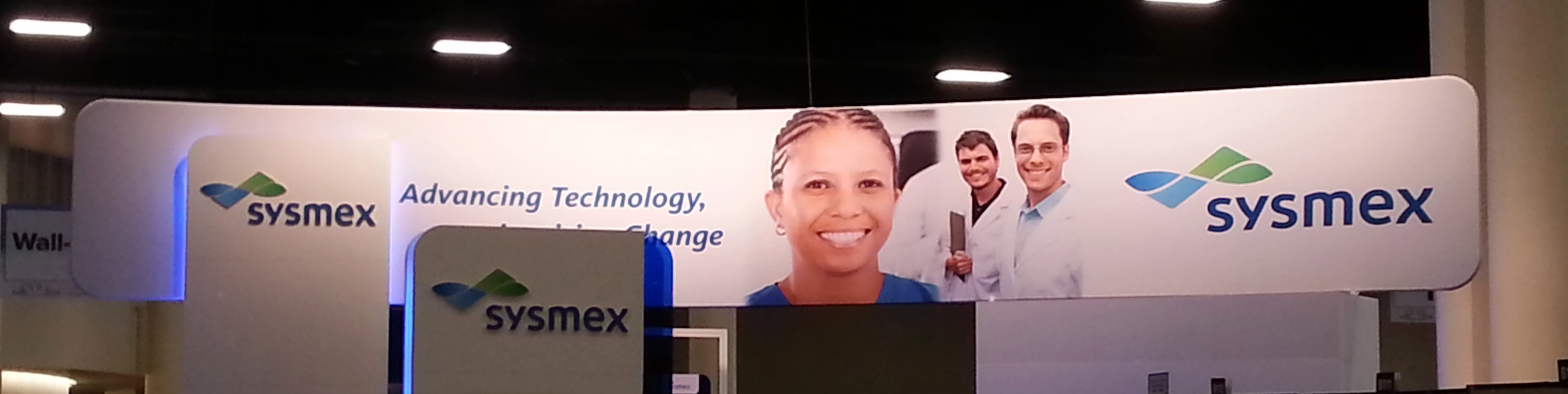 sysmex wide curved trade show hanging sign suspended above booth